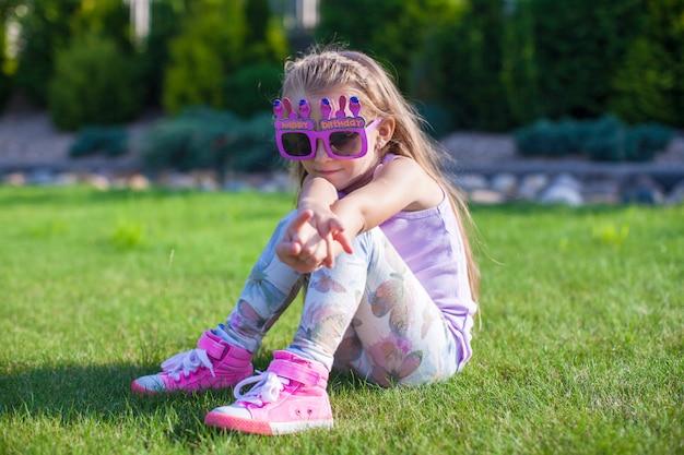 Adorável menina com óculos de feliz aniversário sorrindo ao ar livre