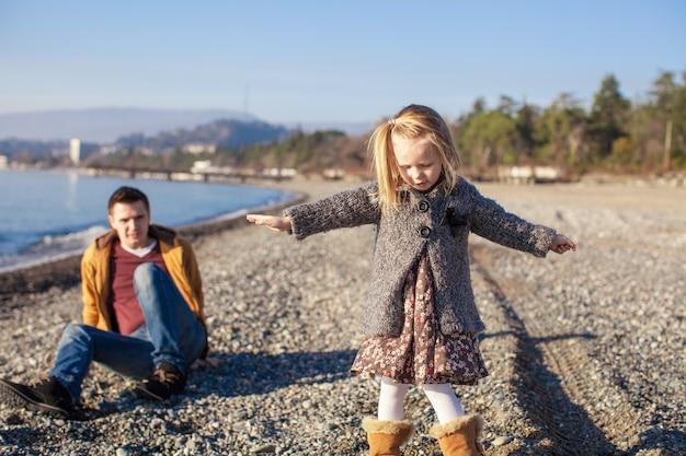 Adorável menina com pai se divertindo na praia em dia quente de inverno