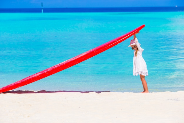 Adorável menina com prancha vermelha grande na praia tropical branca