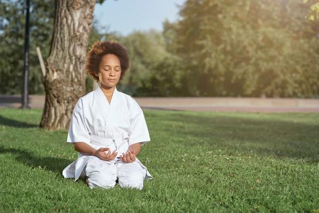Adorável menina com quimono de caratê meditando ao ar livre