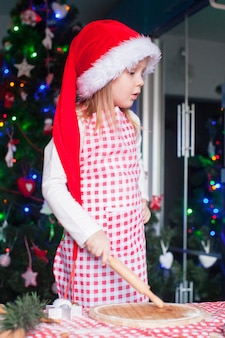 Adorável menina com rolling pin assar biscoitos de gengibre para o natal