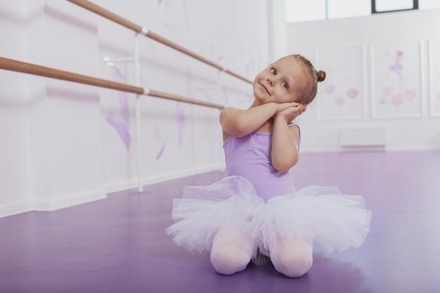 Adorável menina com roupa de balé praticando na aula de dança
