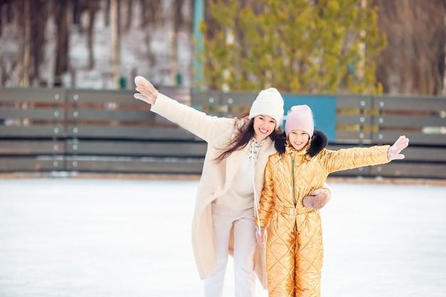 Adorável menina com sua mãe patinando na pista de gelo