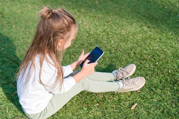 Adorável menina com telefone durante as férias de verão ao ar livre