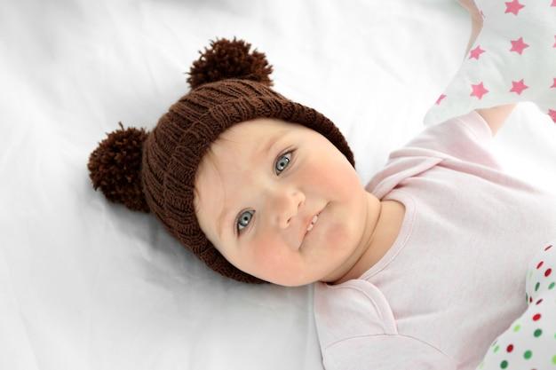 Adorável menina com um chapéu e um lençol branco
