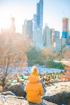 Adorável menina com vista para a pista de gelo no central park em nova york