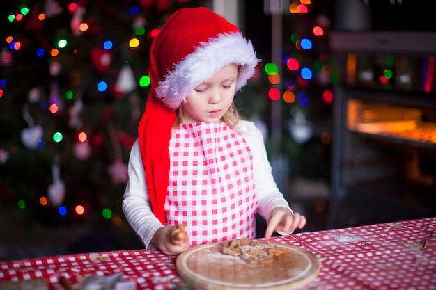 Adorável menina comendo a massa para biscoitos de gengibre na cozinha
