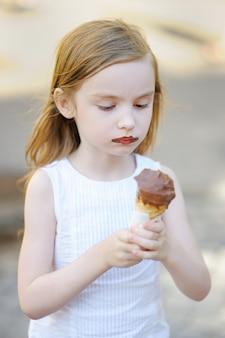 Adorável menina comendo sorvete ao ar livre no verão