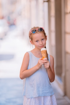 Adorável menina comendo sorvete ao ar livre no verão.