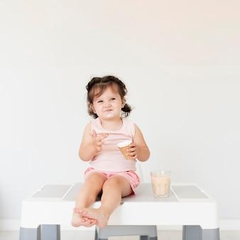 Adorável menina comendo sorvete no gelo
