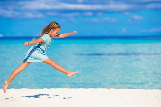 Adorável menina correndo durante as férias de praia