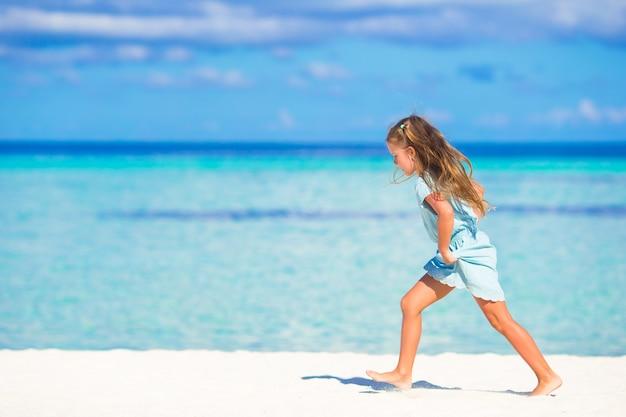 Adorável menina correndo na praia branca tropical