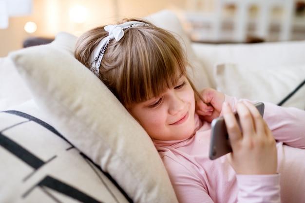 Adorável menina criança bonita olhando no celular enquanto estava deitado no sofá.