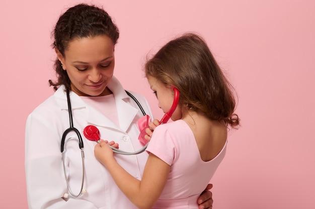 Adorável menina criança de 4 anos brincando de médico, usando o estetoscópio, ouvindo a respiração do médico no peito e nos pulmões com fita rosa no peito. conceito de programa educacional para apoiar pacientes com câncer