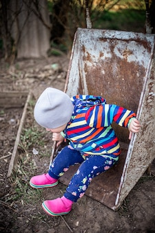 Adorável menina criança sentada em um carrinho de mão na fazenda fazendo e jardinando para crianças pequenas