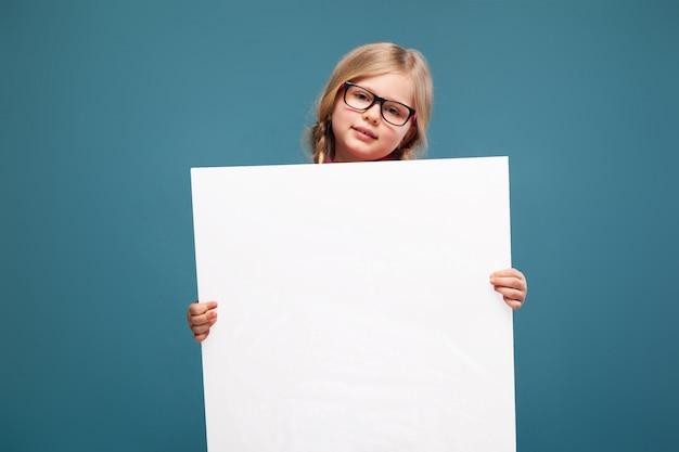 Adorável menina de camisa rosa, calça preta e óculos contém cartaz em branco vazio