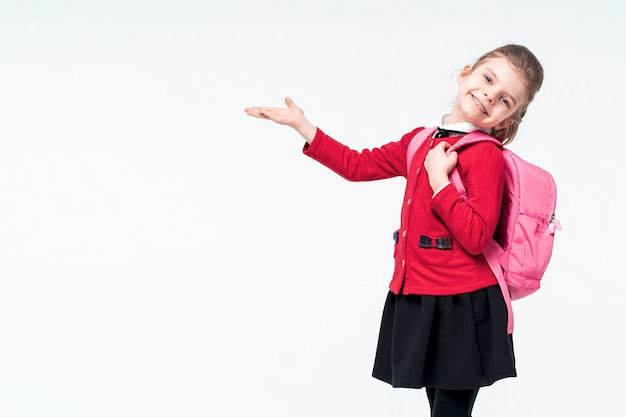 Adorável menina de casaco vermelho, vestido preto, mochila apontando