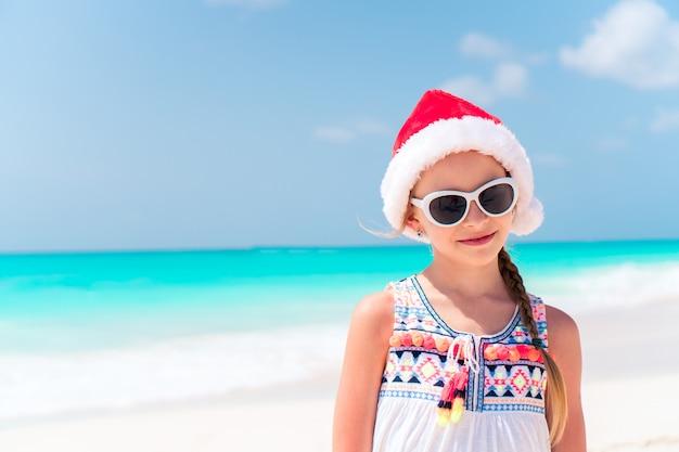Adorável menina de chapéu de papai noel durante as férias de praia de natal