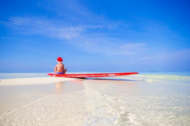 Adorável menina de chapéu de papai noel na praia durante as férias