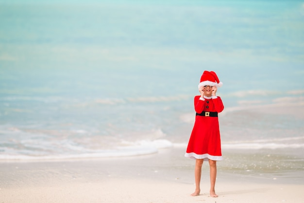 Adorável menina de chapéu de papai noel na praia tropical