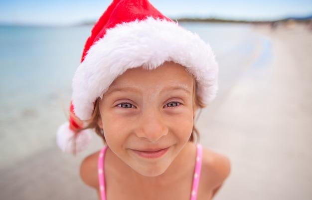 Adorável menina de chapéu de papai noel vermelho na praia tropical