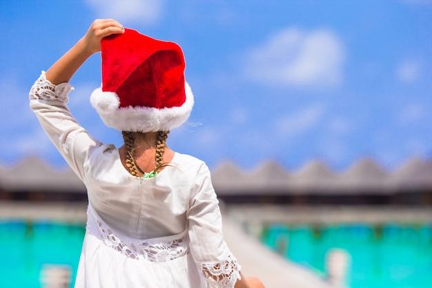 Adorável menina de chapéu de papai noel vermelho na praia