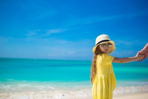 Adorável menina de chapéu na praia durante as férias de verão
