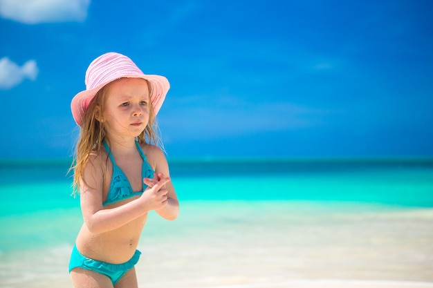 Adorável menina de chapéu na praia durante as férias do caribe