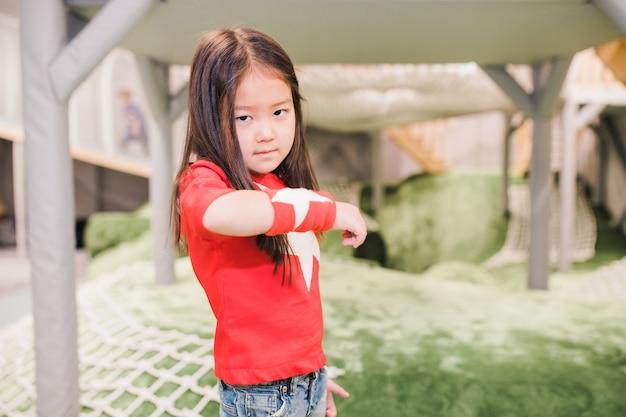 Adorável menina de etnia asiática vestindo camiseta vermelha e alça com estrelas brancas brincando no jardim de infância