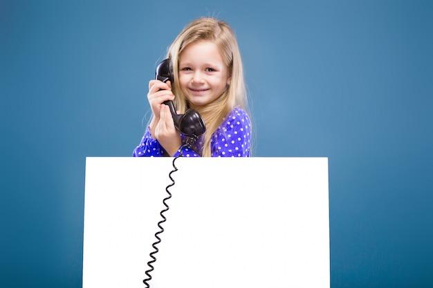 Adorável menina de vestido roxo detém letreiro em branco vazio e telefone aparelho