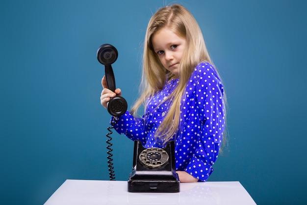 Adorável menina de vestido roxo detém telefone auscultador