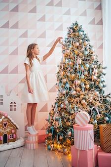 Adorável menina decorando a árvore dentro de casa