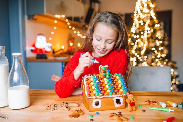 Adorável menina decorando a casa de pão de mel com esmalte. linda cozinha com luzes e árvore de natal, mesa com velas. feliz natal e boas festas