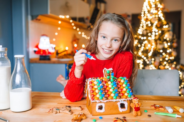 Adorável menina decorando casa de pão de gengibre com esmalte