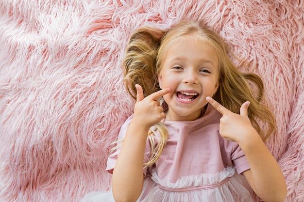 Adorável menina deitada no cobertor de pele rosa