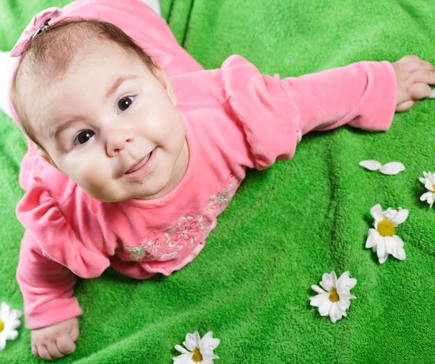 Adorável menina deitada no prado sorrindo