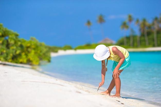 Adorável menina desenho na praia branca