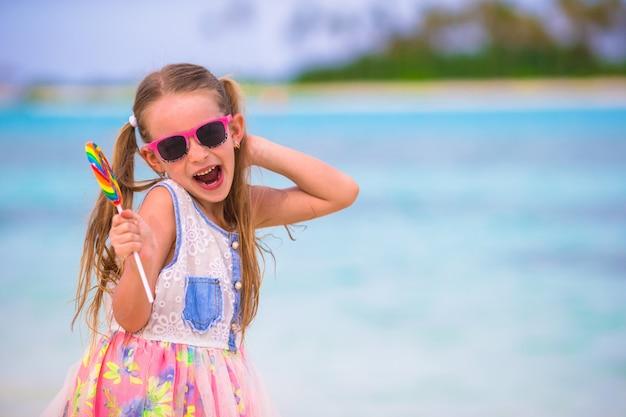 Adorável menina divirta-se com pirulito na praia