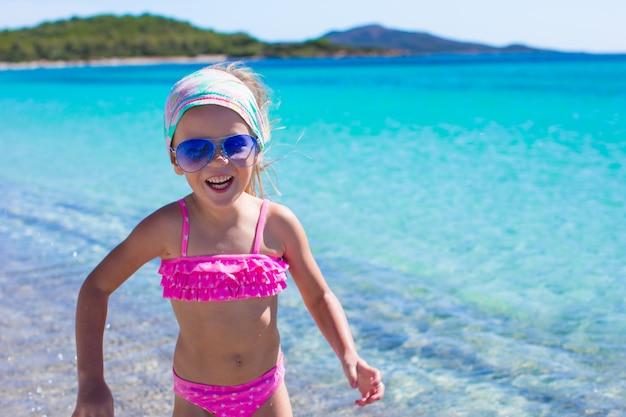 Adorável menina divirta-se em águas rasas na praia tropical