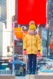 Adorável menina divirta-se na times square, em nova york