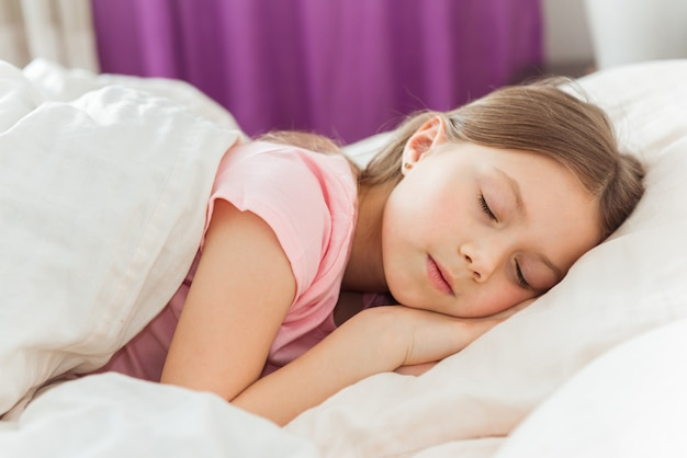 Adorável menina dormindo na cama