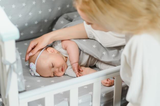 Adorável menina dormindo no berço. criança tirando uma soneca no berço. criança descansando no berçário