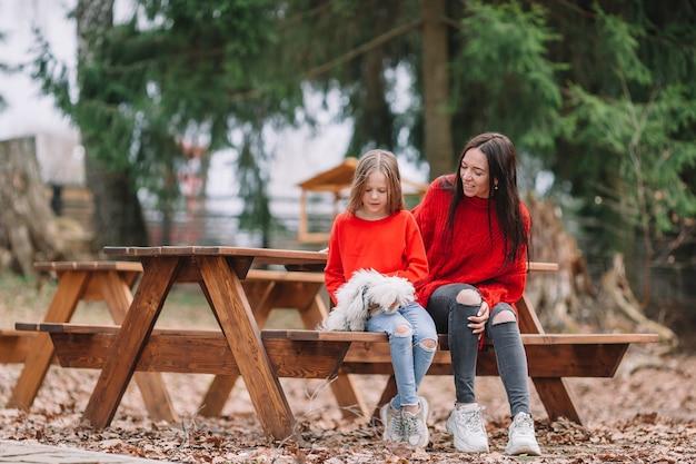 Adorável menina e jovem mãe com cachorro ao ar livre