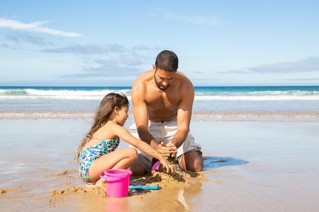 Adorável menina e o pai construindo um castelo de areia na praia, sentados na areia molhada e curtindo as férias