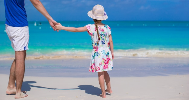 Adorável menina e pai na praia durante as férias de verão