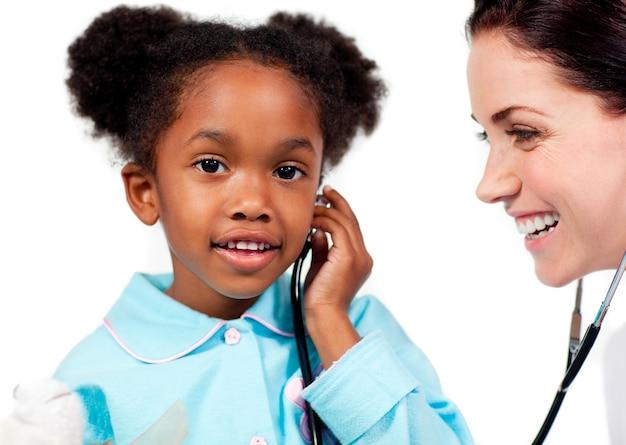 Adorável menina e seu médico brincando com estetoscópio