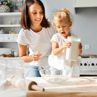 Adorável menina e sua mãe cozinhando juntos
