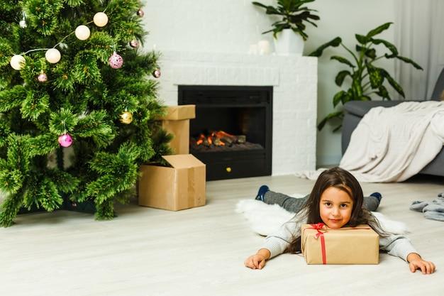 Adorável menina encontra-se debaixo da árvore de natal por uma lareira na véspera de natal
