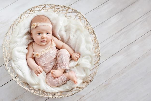 Adorável menina encontra-se em uma cesta