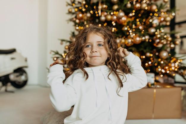 Adorável menina engraçada vestida com roupas brancas e se divertindo em frente a árvore de natal